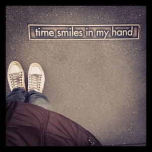 Ps da Talita sobre uma calada escrito &quot;time smiles in my hand&quot;